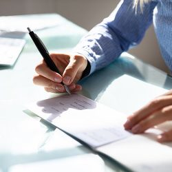 Close-up Of A Businesswoman's Hand Signing Cheque